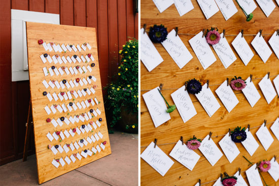 wildflower escort card display on a wooden board - grey calligraphy on white paper with colorful florals