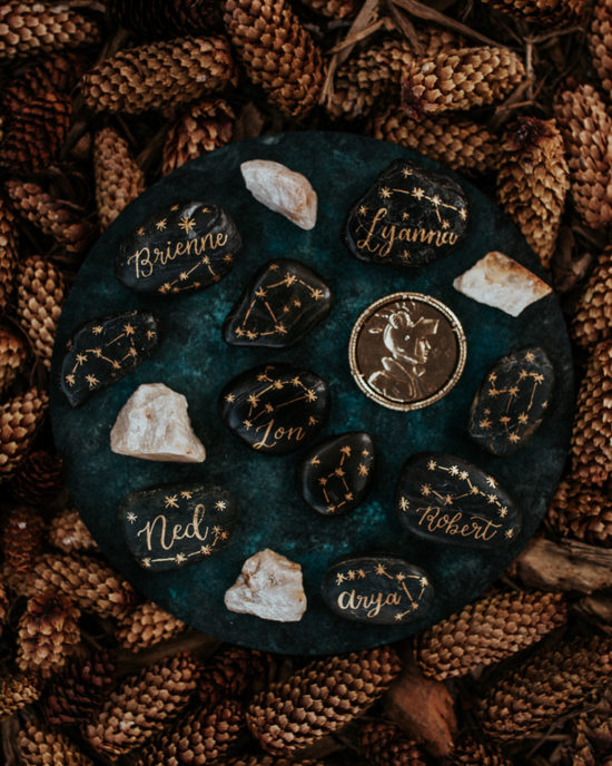 Celestial Game of Thrones Wedding Inspiration - gold calligraphy place cards with constellations on earthy river rocks