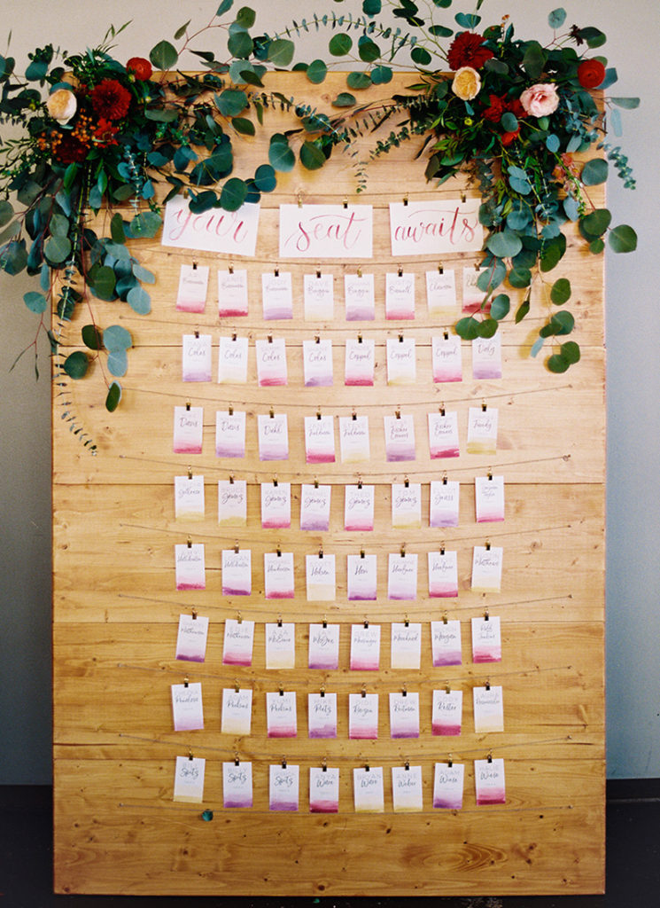 Escort Card Display - Watercolor Wash Cards on wooden display wall - Urban Fall Wedding