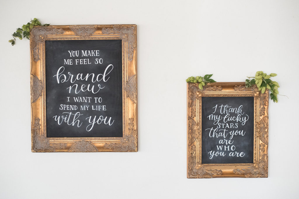 hand lettered wedding signs on chalkboard in gold frames song lyrics